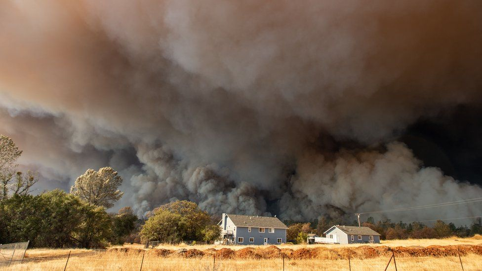 A home is overshadowed by towering smoke plumes as the Camp fire races through California on November 8 2018
